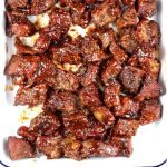 Poor Man's Burnt Ends with bbq sauce on a baking pan