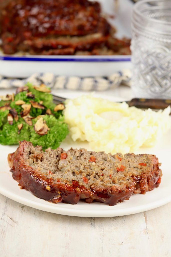 Slice of meatloaf with mashed potatoes and broccoli on a plate, sliced meatloaf on serving dish in background