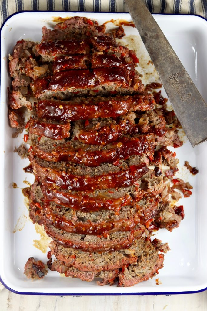 Grilled BBQ Meatloaf sliced over head view on a white platter