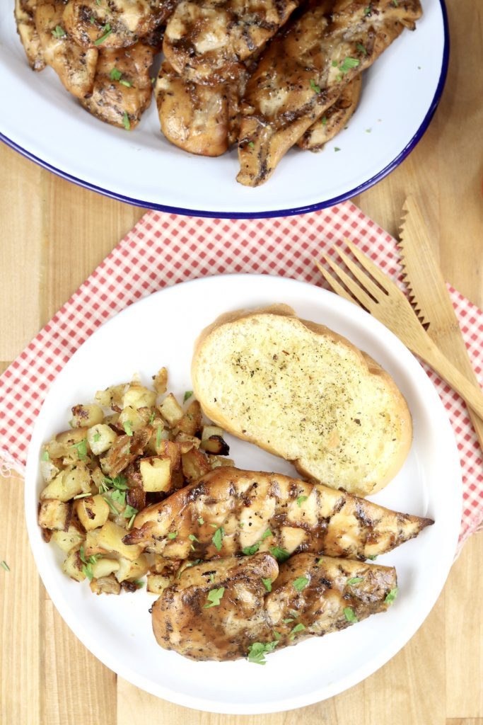 Platter of grilled chicken tenders, plate of chicken tenders with roasted potatoes and garlic bread
