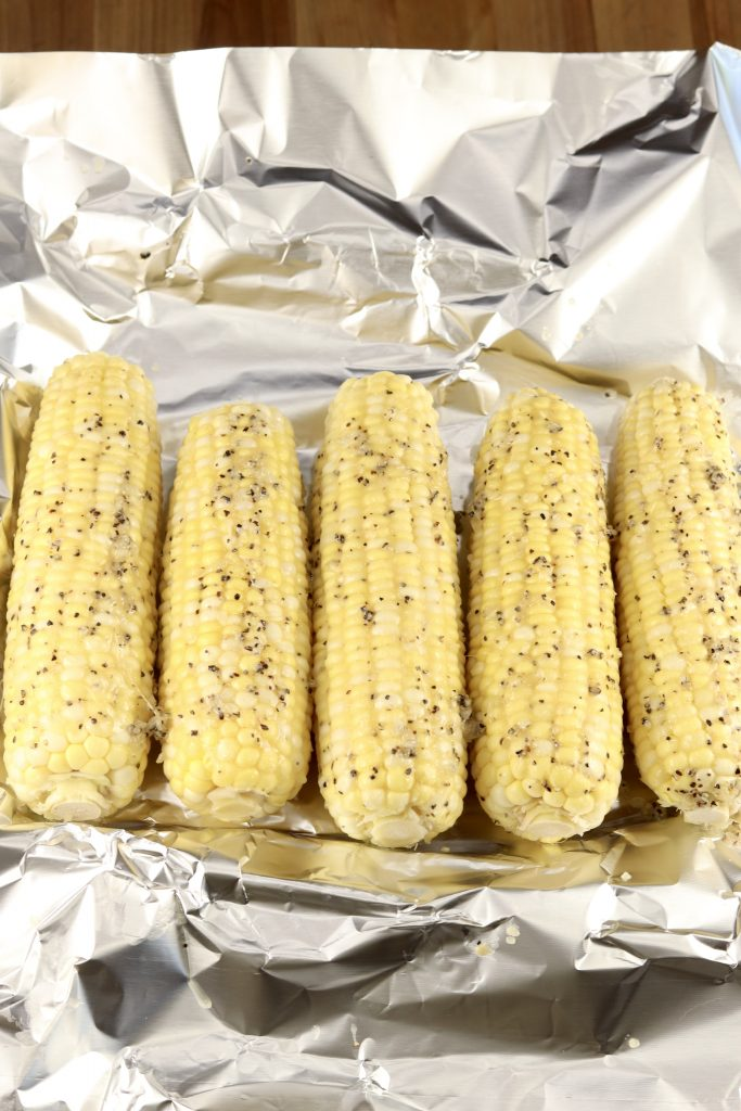 5 ears of garlic butter corn on the cob on a foil lined pan