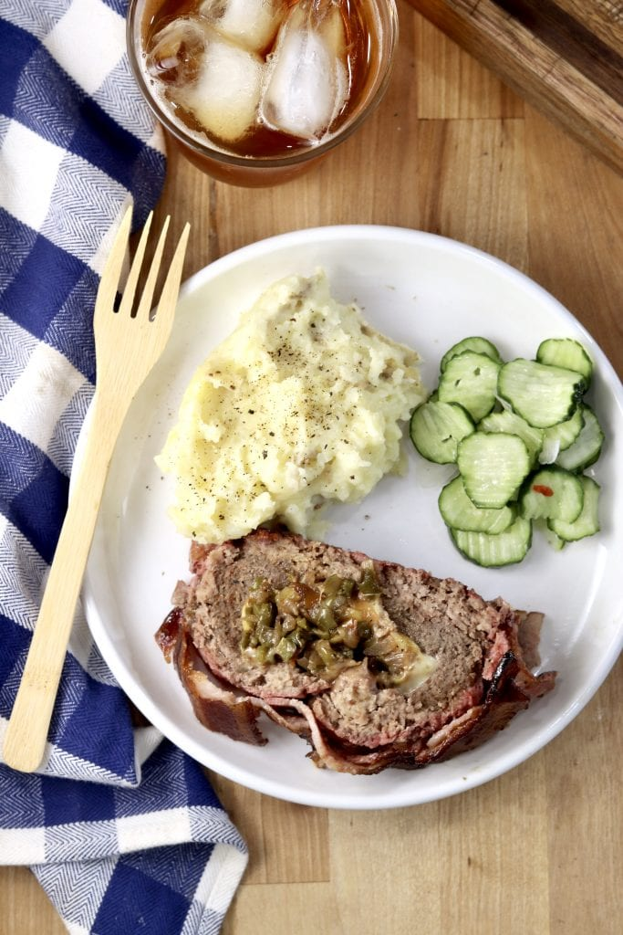 Sliced BBQ Fatty with mashed potatoes and cucumbers on a plate