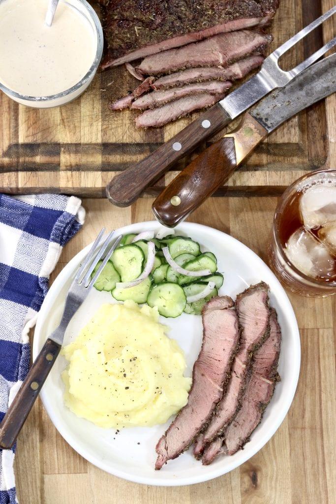 Plate of sliced roast, mashed potatoes, cucumber salad, glass of tea, horseradish sauce and roast on a cutting board, sliced