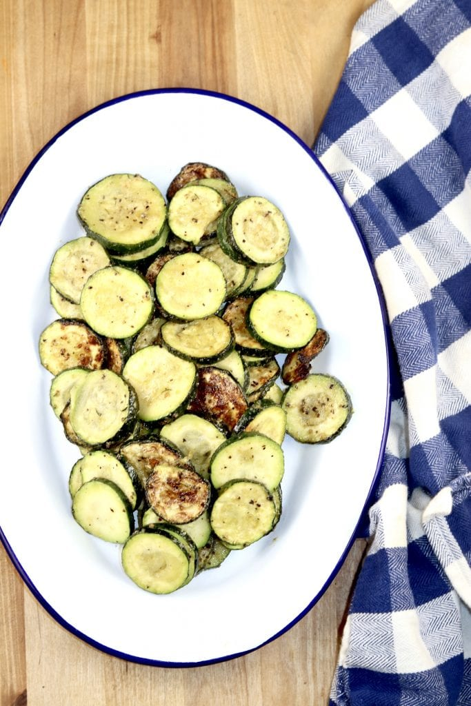 Grilled Zucchini on a white oval platter, blue check napkin to the side