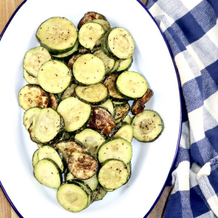 Grilled Zucchini on a white oval platter - blue napkin on side