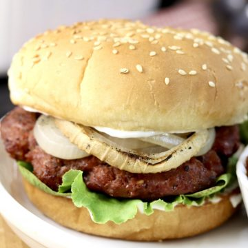 Grilled Burgers on a sesame bun with lettuce and grilled onion
