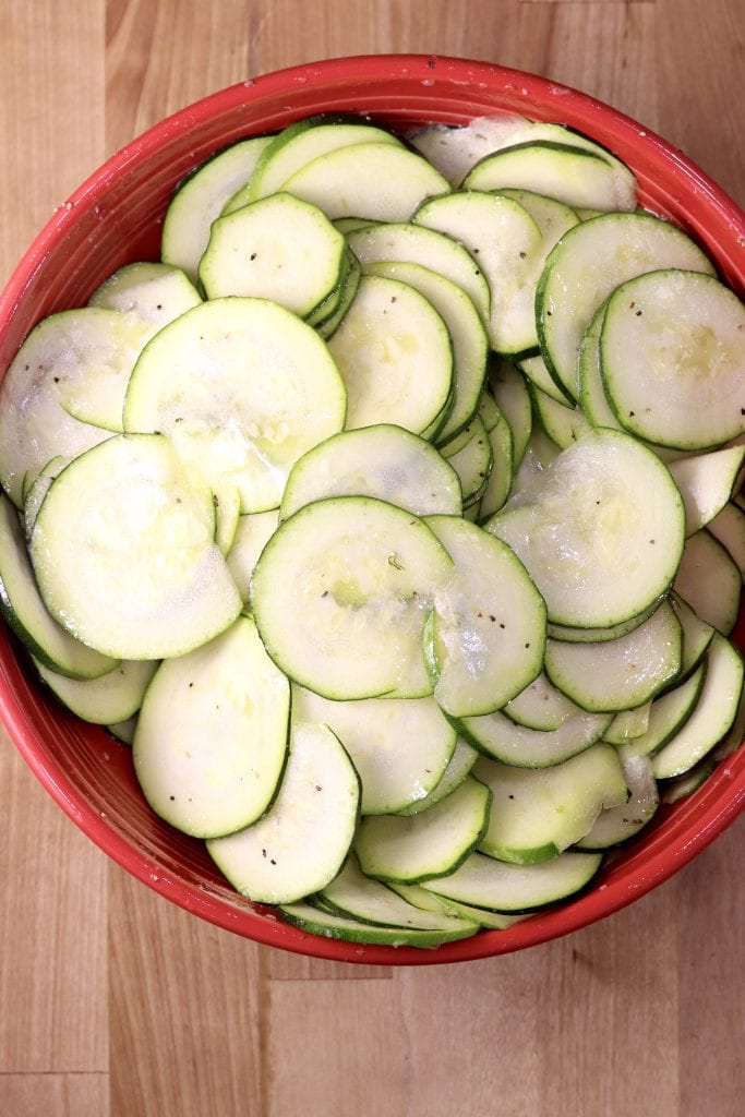 Bowl of sliced zucchini with olive oil, salt, pepper and garlic
