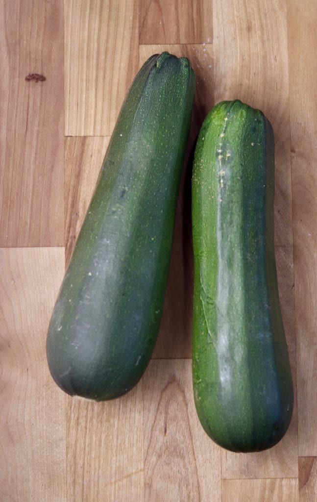 2 fresh zucchini on a butcher block