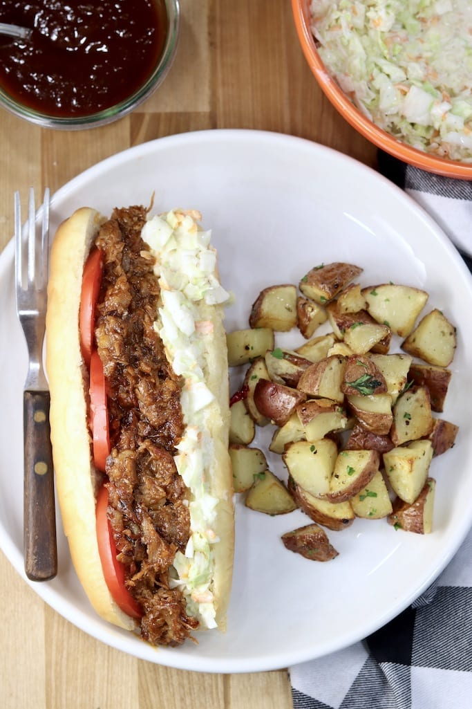 Brisket Hoagie with slaw and tomatoes plated with potatoes