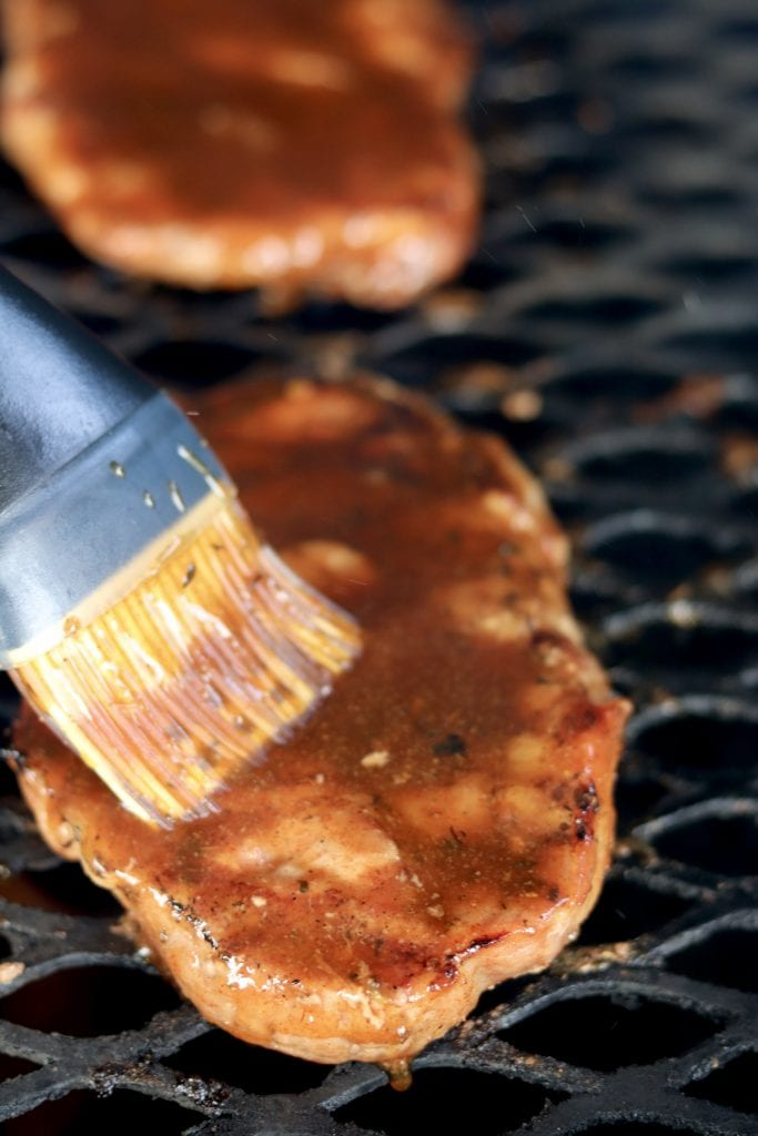 Brushing Coca-Cola Glaze over grilled pork steaks