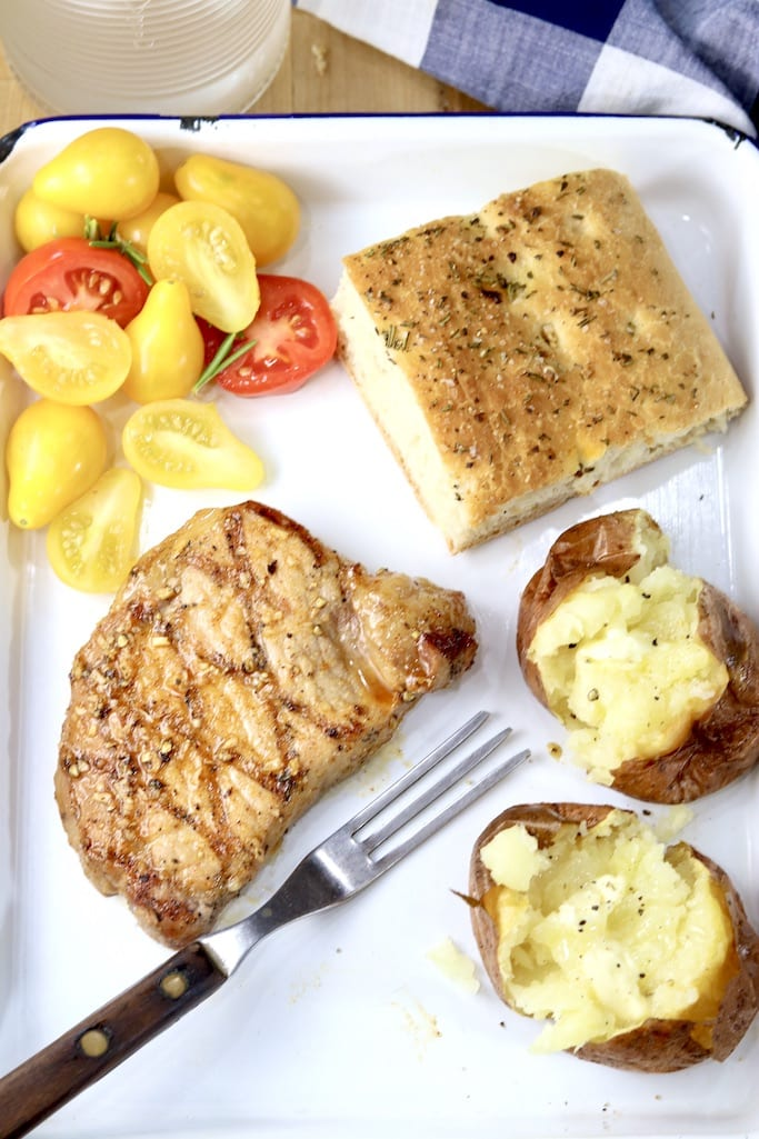 Grilled pork chops with sliced tomatoes, baked potato and focaccia bread
