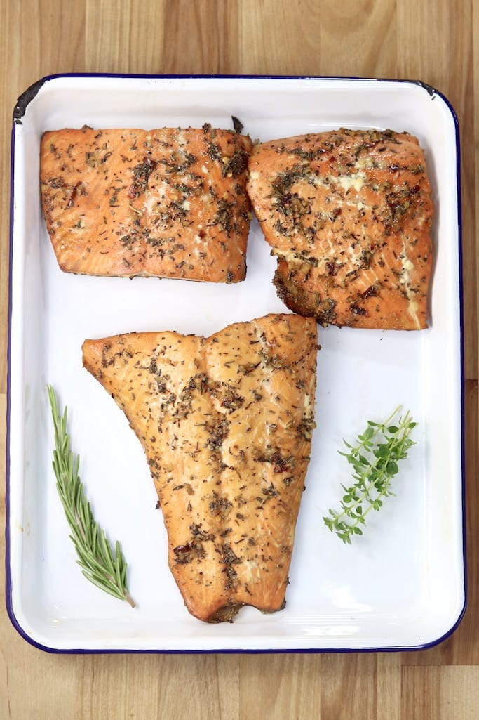 Salmon with herbs on a white plate