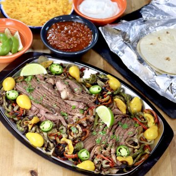 Grilled Steak Fajitas platter with toppings and flour tortillas