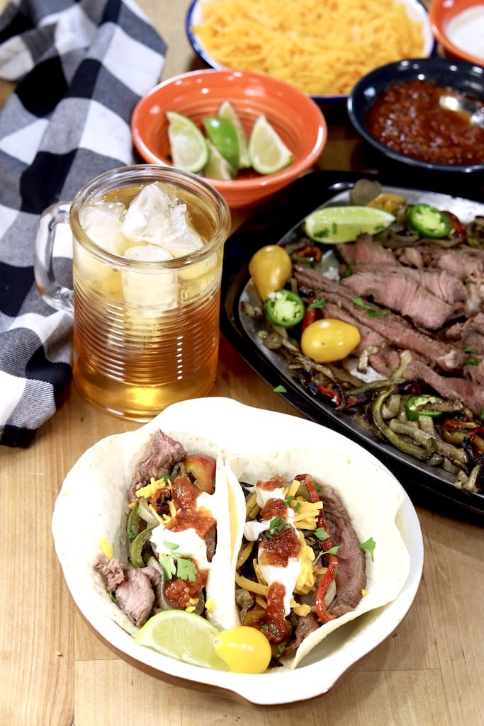 Plate of grilled steak fajitas with ice tea