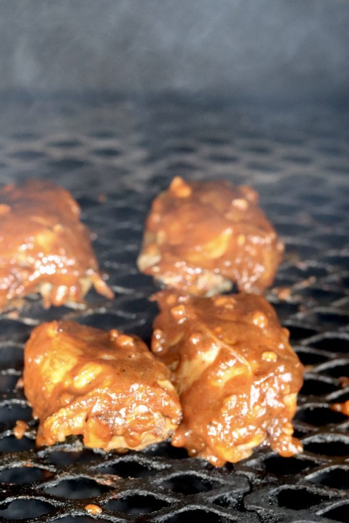 grilled chicken thighs with peanut sauce on the grill