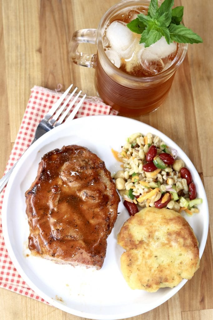 Pork Steak on a plate with potato cake and barley and bean salad, glass of ice tea