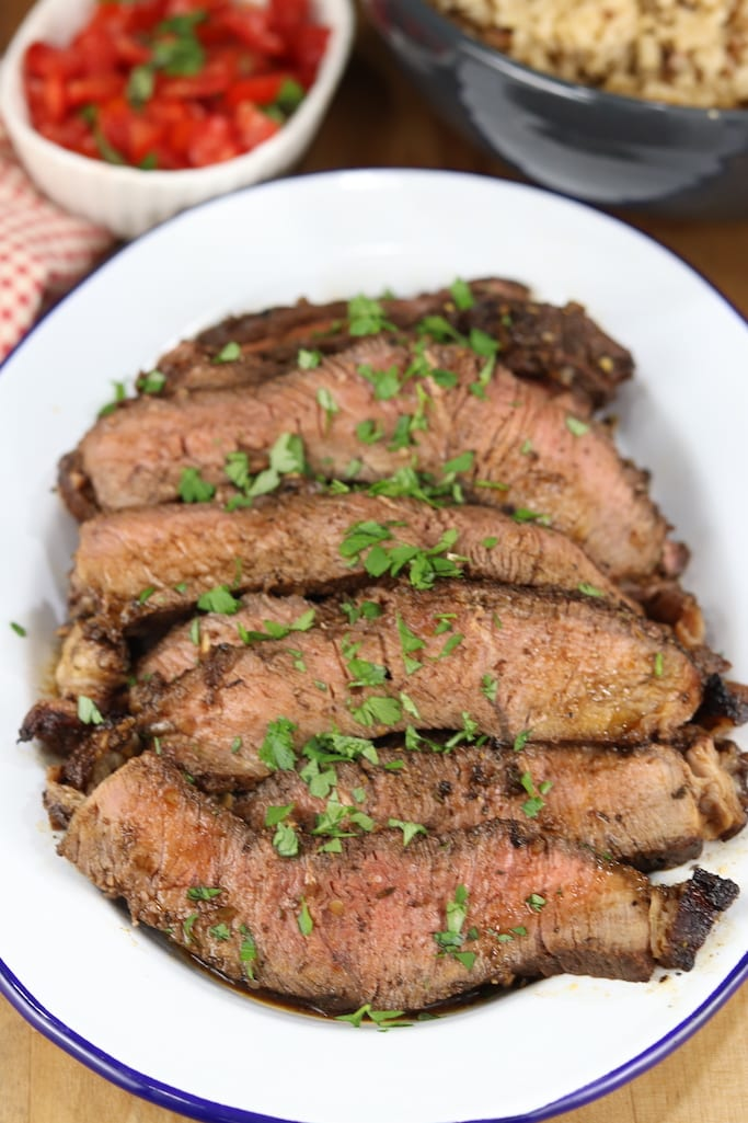 Thin sliced balsamic roast on a platter garnished with herbs