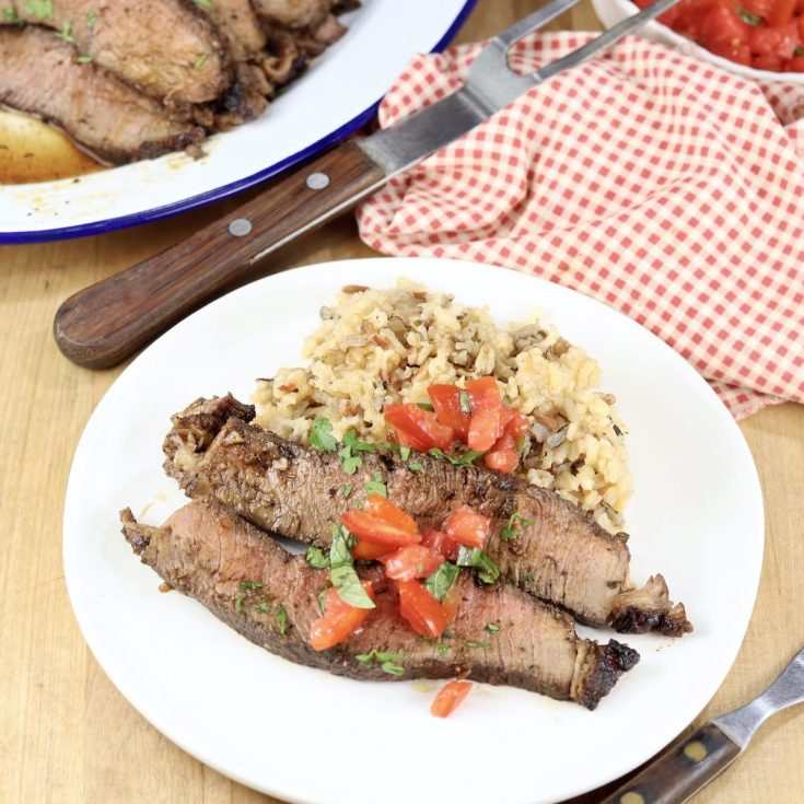 Sliced roast beef with tomato and basil garnish over rice pilaf