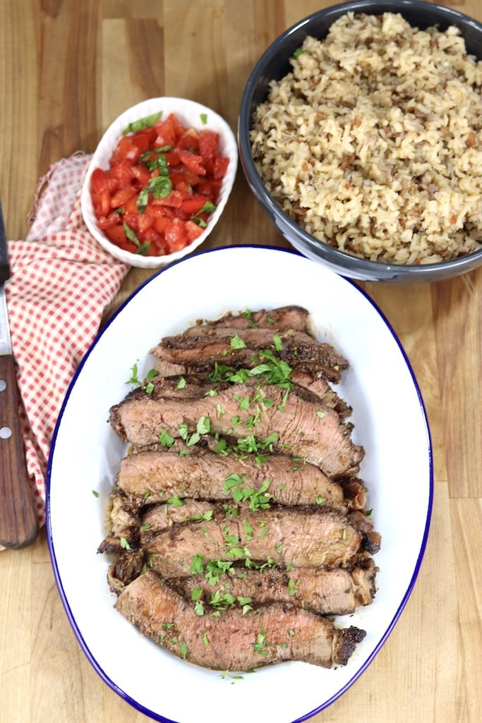 Platter of sliced roast beef, bowl of chopped tomatoes with basil, bowl of rice pilaf