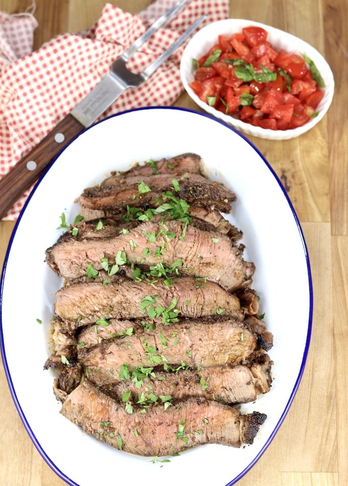Sliced roast beef on an oval white platter, bowl of chopped tomatoes and basil in top corner, meat fork on a napkin