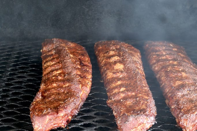 Baby Back ribs on the grill - smoke rolling over 3 racks of ribs