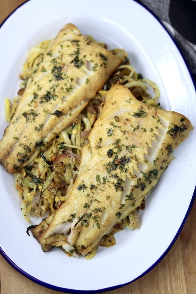 Garlic butter fish with zucchini noodles on a platter