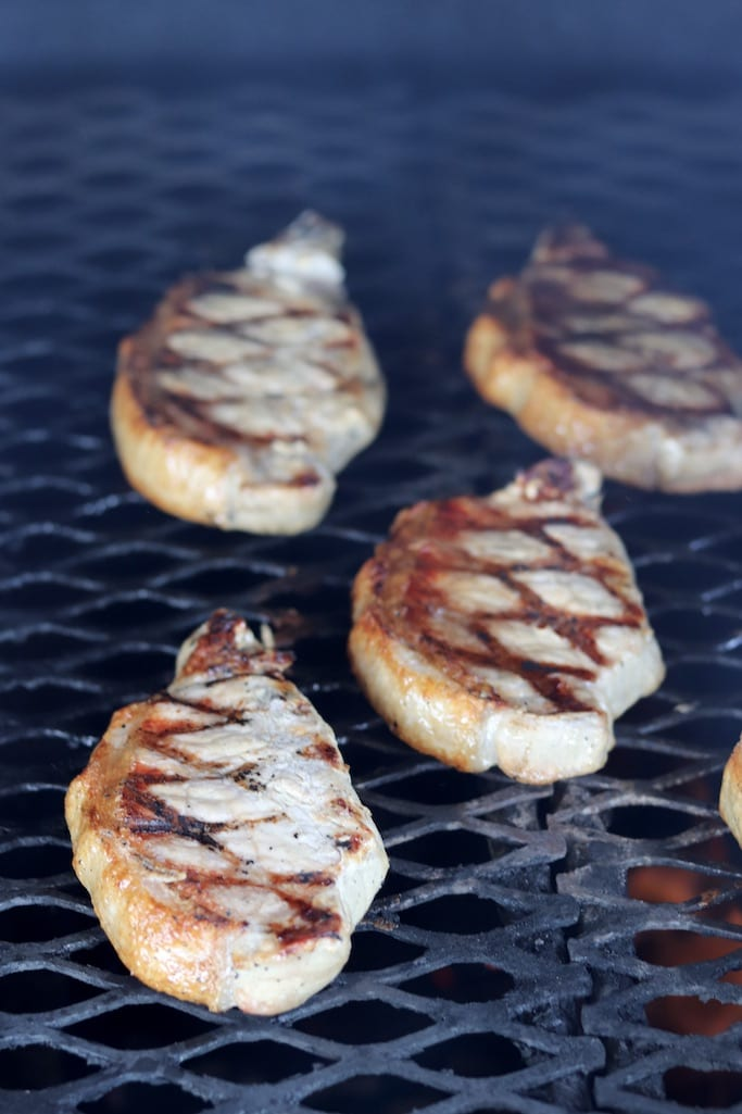 Boneless Pork Chops on the grill with grill marks on the pork chops