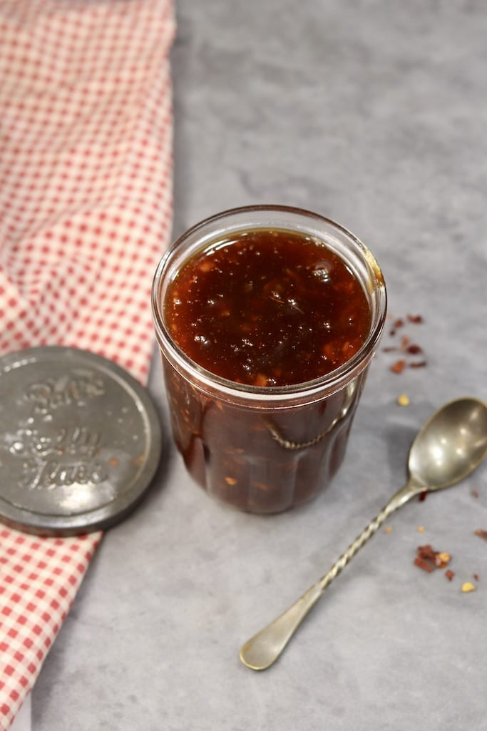 Peach BBQ Sauce in a small jar with lid, spoon and red check napkin on a gray board