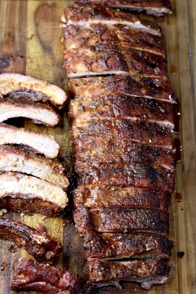 Baby back ribs, sliced on a cutting board with whole rack to the side.