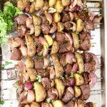 Steak, Potato Kabobs with onions and parsley garnish on a sheet pan