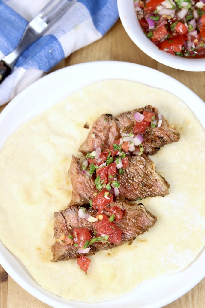 Sliced roast beef on a flour tortilla topped with pico de gallo