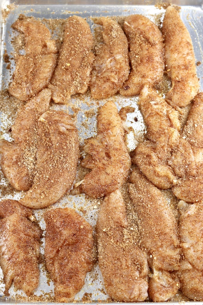 Brown sugar rubbed chicken tenders on a sheet pan for grilling