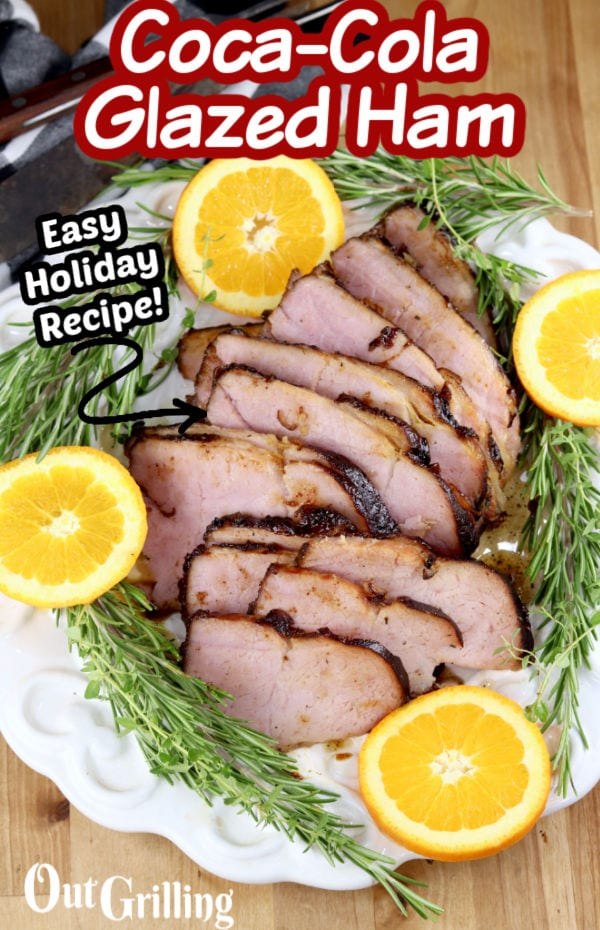 Coca-Cola Glazed Ham -text overlay with sliced ham, orange slices and rosemary on a serving plate