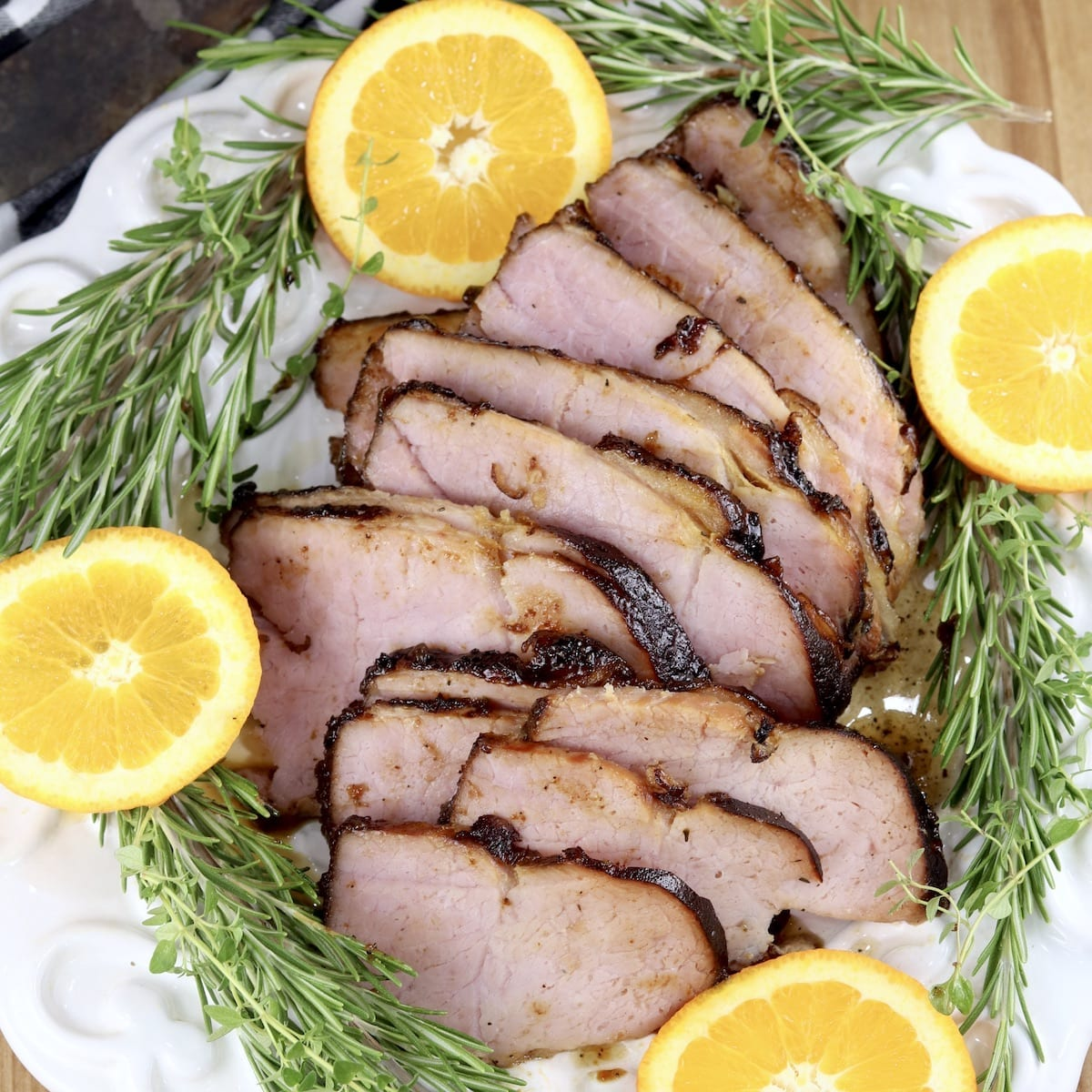 Coca-Cola Glazed Ham, sliced on a platter with fresh rosemary sprigs and sliced oranges