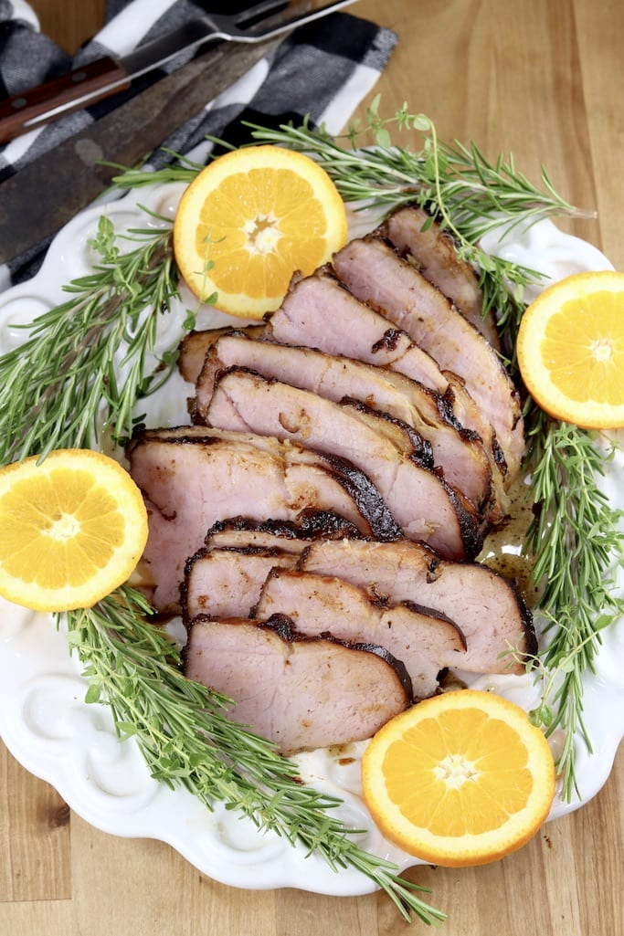 Sliced ham platter with orange slices and rosemary sprigs overhead view