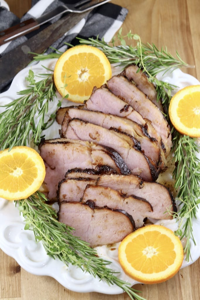 Sliced Coca-Cola Ham platter with oranges and rosemary