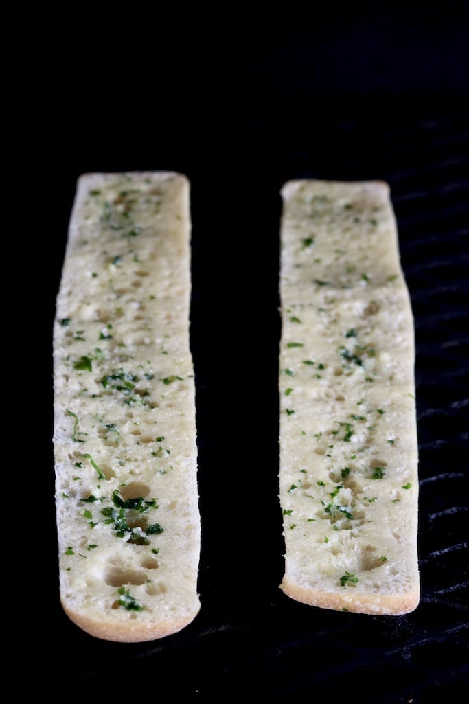 Sliced baguette with garlic butter on the grill