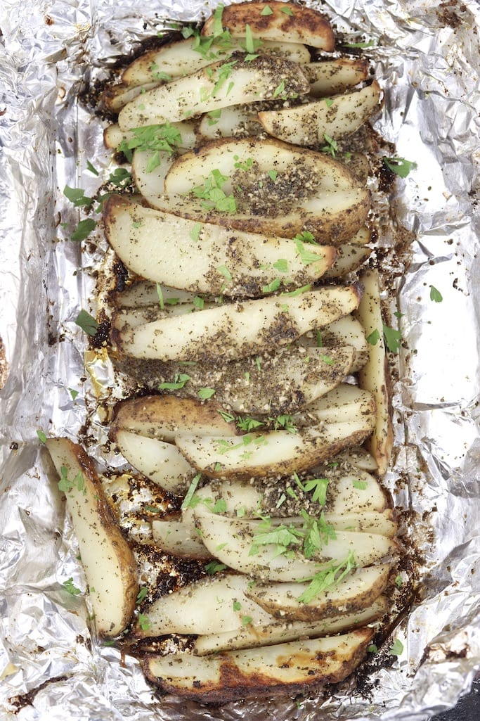 Foil packet with grilled potato wedges in garlic and rosemary garlic butter