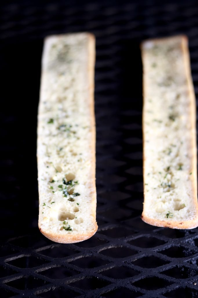 Toasting sliced baguette with garlic butter on the grill