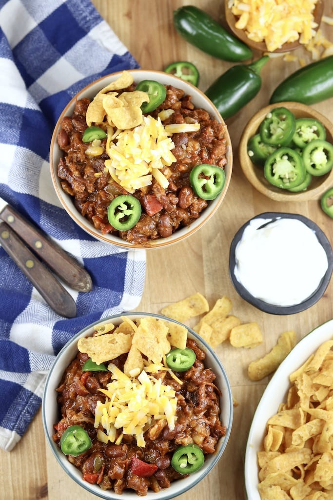 Overhead view of 2 bowls of chili with cheese, jalapenos, corn chips, sour cream and sliced jalapenos in bowls