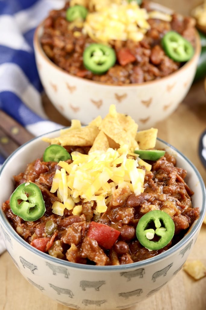 2 bowls of chili topped with sliced jalapenos, sliced cheese and Fritos
