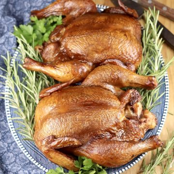 2 Apple Cider Smoked Whole Chickens on a platter with fresh rosemary garnish