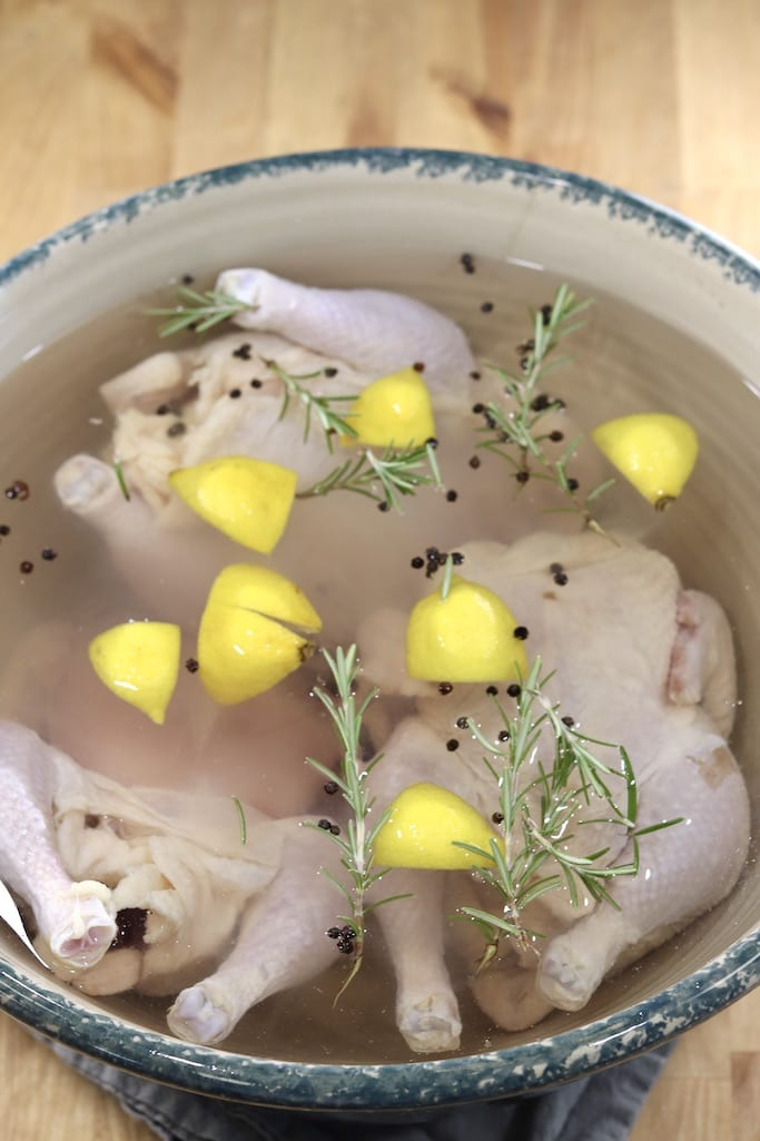 Brining 3 chickens in a large bowl with lemons, rosemary and peppercorns