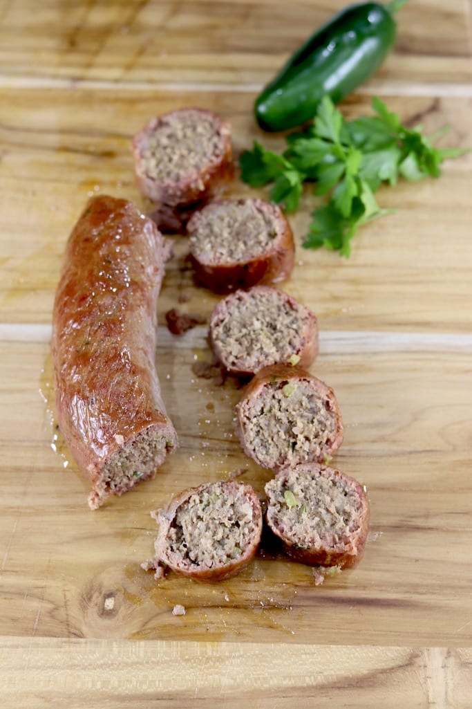 Wood board with smoked sausage slices and link with jalapeno and fresh parsley