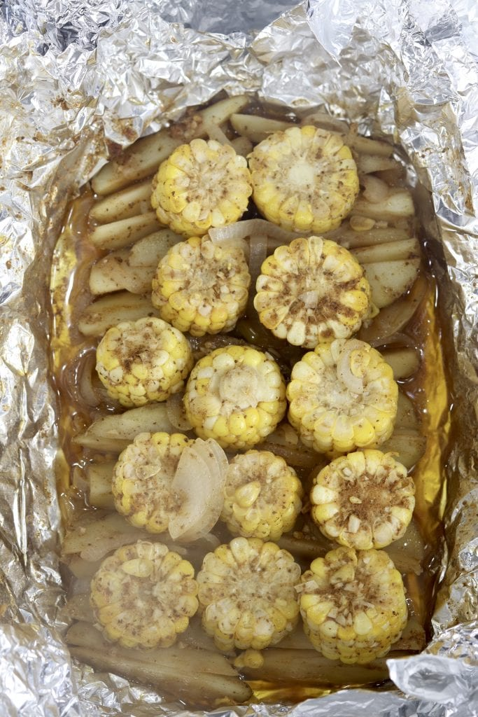 Foil packet with potatoes, onion and corn on the cob