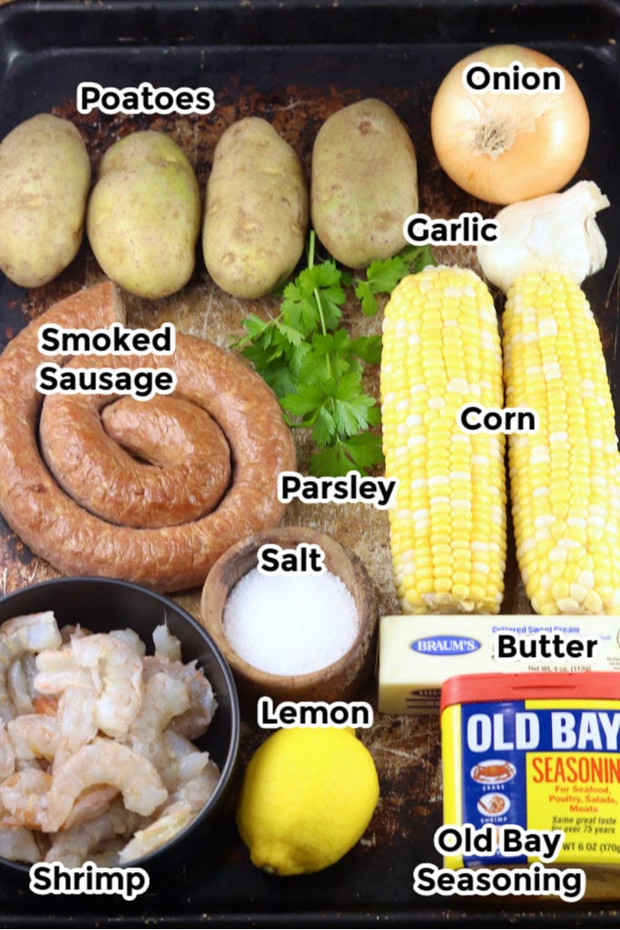 Ingredients for shrimp boil packets on a sheet pan with text labels