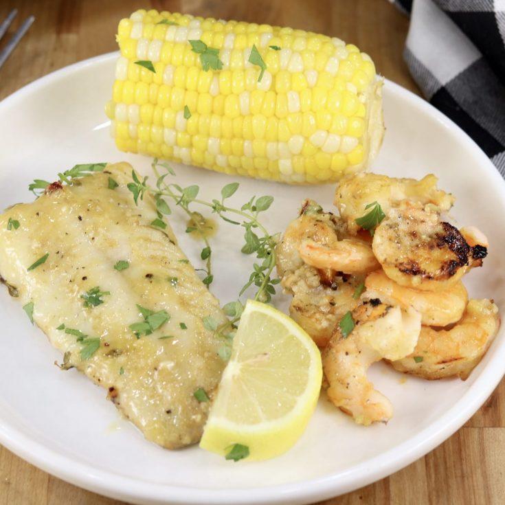 Lemon Garlic Fish and Shrimp with corn on the cob on a plate, lemon wedge garnish
