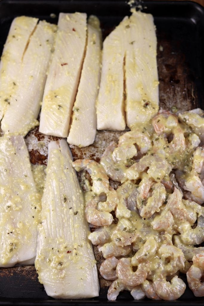 Fish filets and shrimp on a sheet pan brushed with lemon garlic sauce