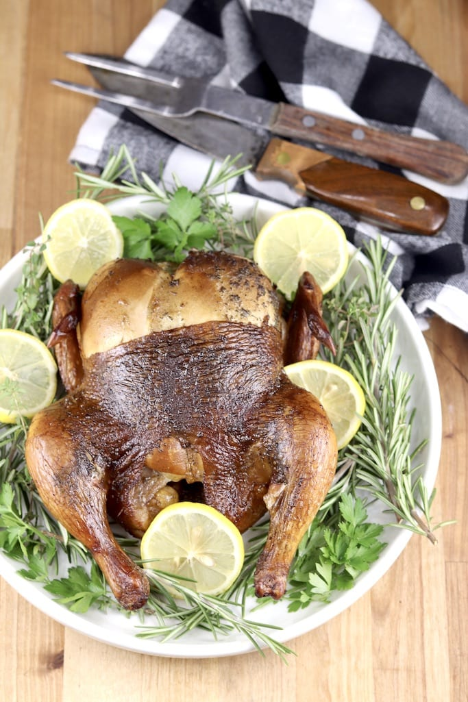 Whole grilled chicken overhead view with lemon slices and rosemary on a white platter