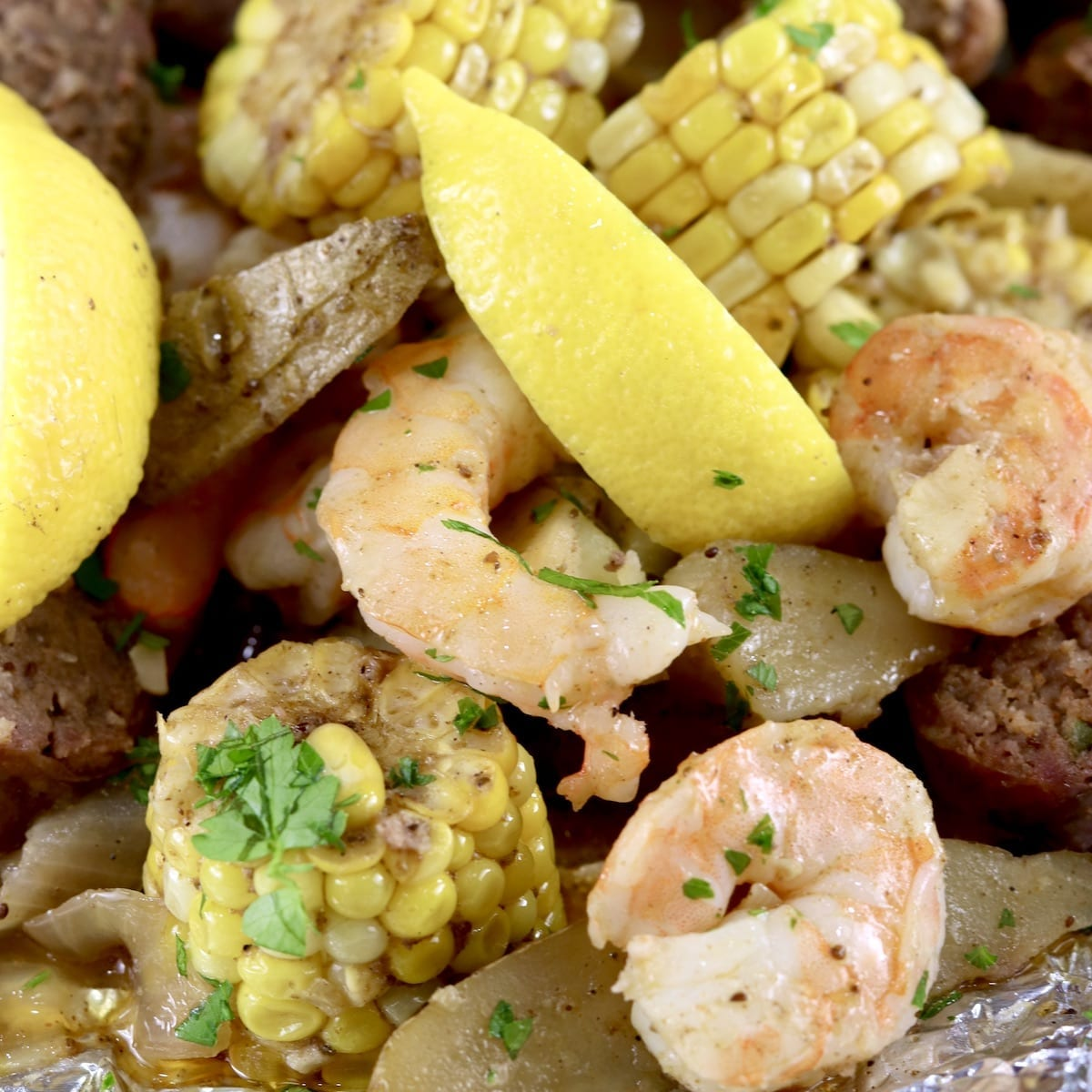 Shrimp Boil made in a foil packet with corn on the cob, potatoes, onions, smoked sausage, lemon